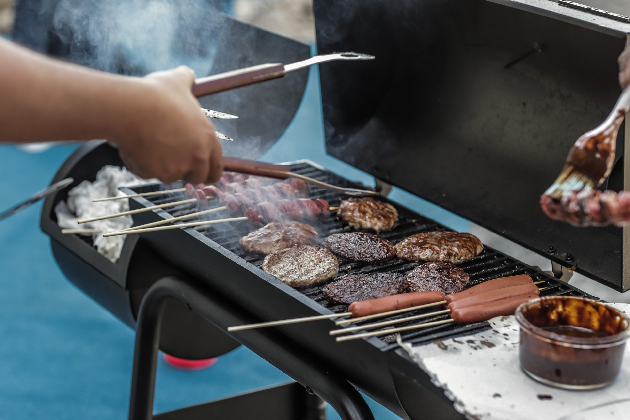 cooking burgers on best grill and griddle combo with tongs in hand